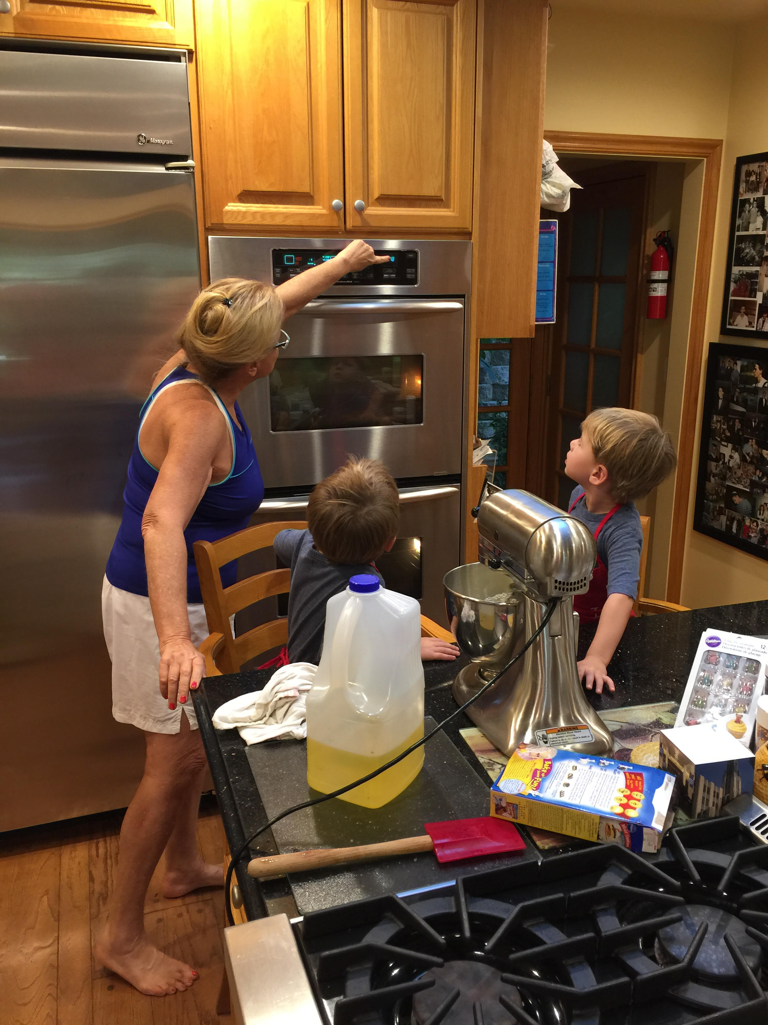 Larraine turning on stove for cupcakes with Noah and Gabe