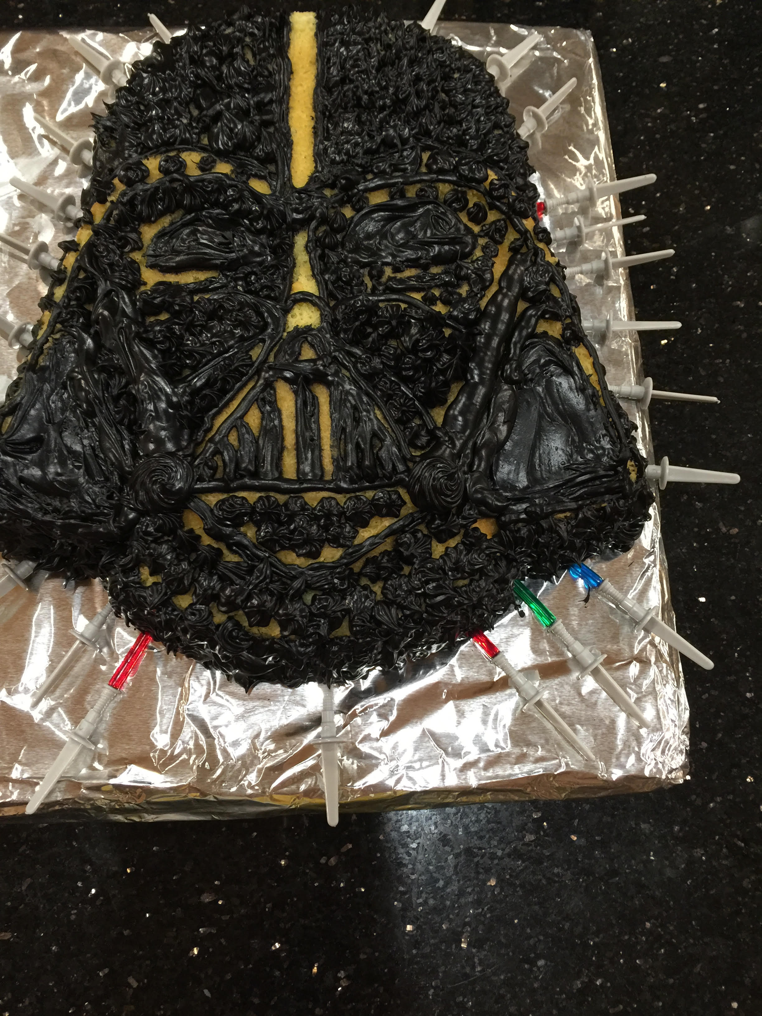 Jacks bday cake Darth Vader with little spears as well as darth vader candles